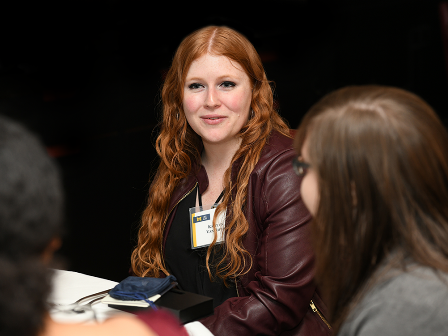 A photograph of Kaitlyn Van Riper sitting at a table with other students. She is wearing a dark red leather jacket with a name tag clipped to the lapel.