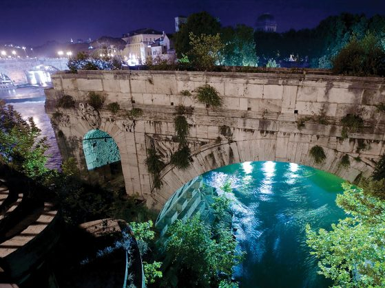 Photograph of the Tiber River flowing beneath an ancient arch.