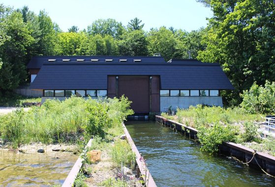 A building is shown from the water, with a brown metal roof and sliding garage door closing off a boat launch.