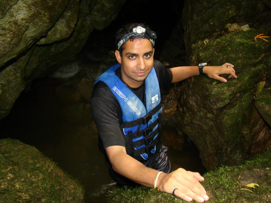 Prosanta Chakrabarty stands in a cave of moss-covered rocks. He wears a life vest and head lamp.