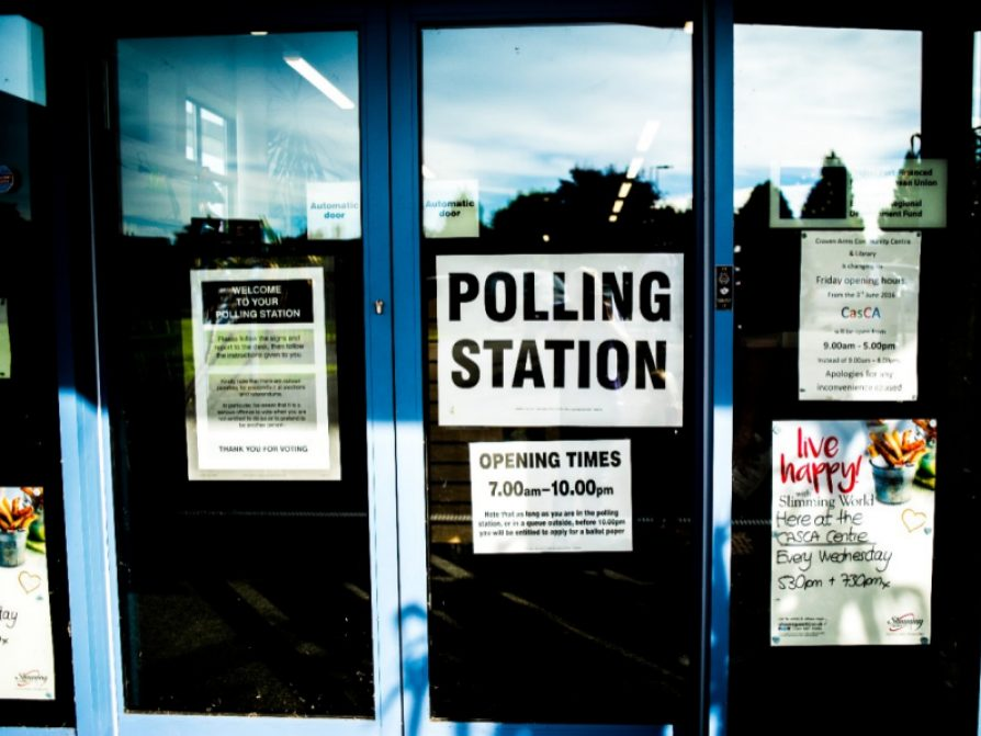 Photograph of a glass door that says polling station and has other community-oriented flyers posted around it.
