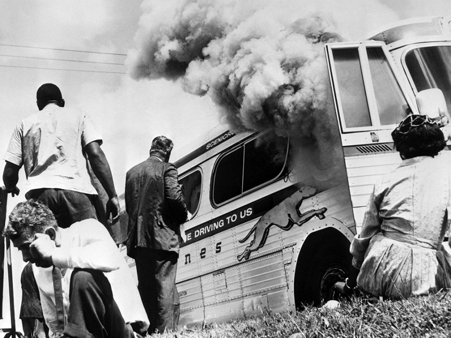A black and white photo of a Greyhound bus with a plume of smoke billowing out its door. A woman sits in the grass looking at it. Another man sits in the grass leaning away from the smoke. Two men are standing facing the bus. The Greyhound slogan, Leave the driving to us, is partially legible on the bus's side.