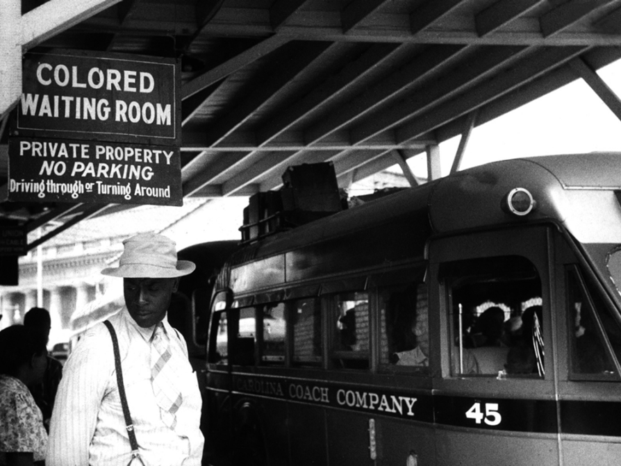 In a black-and-white photograph, a black man stands beneath a sign that says Colored Waiting Room in large letters. Below, in smaller letters, the sign says private property. No parking driving through or turning around. The man is wearing a white hat, a striped shirt, a striped tie, and suspenders. He is looking down to his right. Behind him, seen over his left shoulder, is a bus.