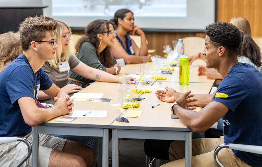 Students sitting side by side at a long table, leaning forward to talk to each other. There are plastic bags of blue and yellow M&Ms in the center of the table, which the students are using as they participate in an interactive game.