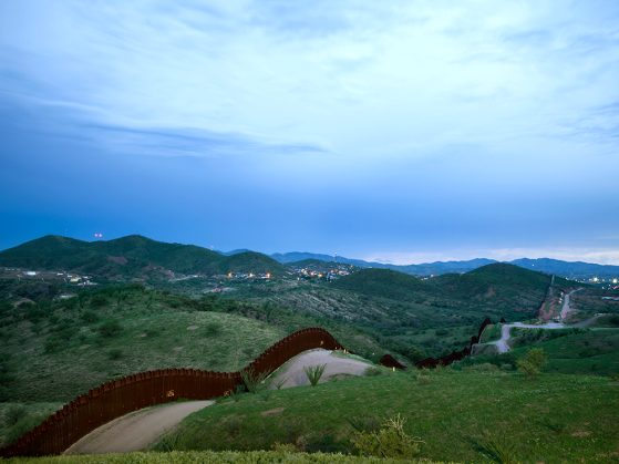 A daytime photograph of the border fence, which runs along a dirt road. There are lush green hills, a bright blue sky, and foothills in the distance.