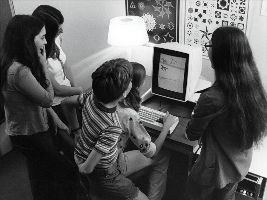 A black and white photograph of five kids gathered around an old computer screen. The screen displays three horses
