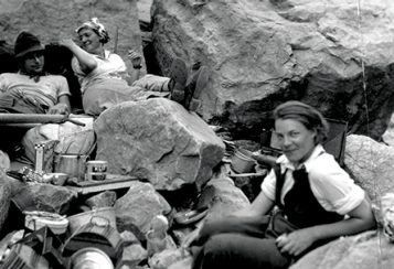 A depression-era photograph of two women, Elzada Clover and Lois Jotter, and two unidentified men sitting among big rocks with camping gear arrayed around them.