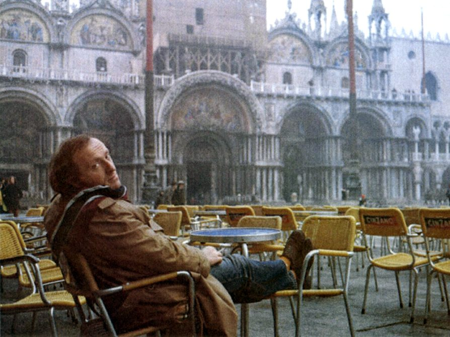 Joseph Brodsky in a Russian square, sitting at an empty outdoor cafe with yellow chairs. He is smoking a cigarette and he has his feet propped up on a chair.