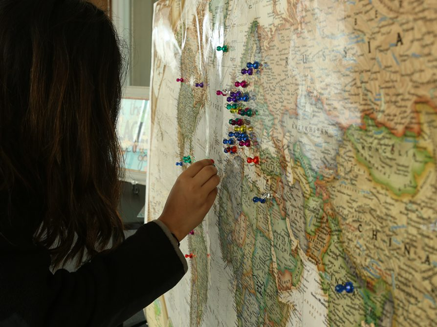 A student stands before a map of the world hanging from a bulletin board. She inserts a pushpin in the northern part of Africa.
