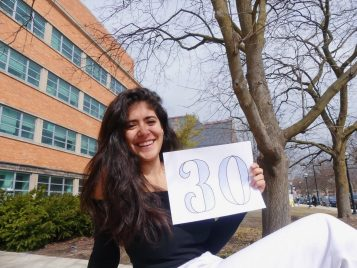 "A student holding a sign that says ""30"""