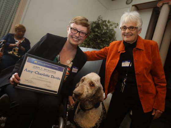 Amy-Charlotte Devitz (with her service dog, Fish) receives her award from Anna Schnitzer, chair, James T. Neubacher Awards Committee and informationist, Taubman Health Sciences Library. Image credit: Kyle Keener, Michigan Photography