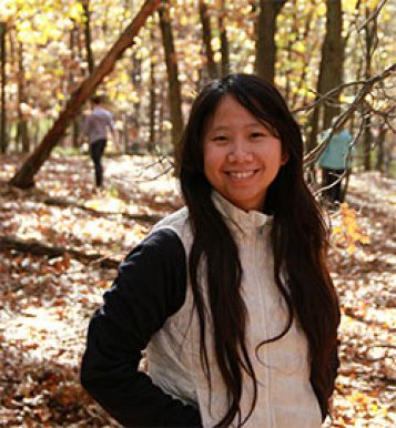 Theresa Wei Ying Ong standing outside in woods in the fall